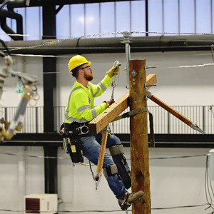 Apprentice lineman scaling a pole in the MidAmerican Training Center for Excellence