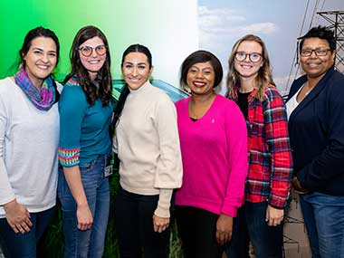 Six women, all MidAmerican employees, standing in front of a mural