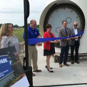 MidAmerican and DMACC representatives cutting a blue ribbon in front of the donated nacelle on the DMACC campus.