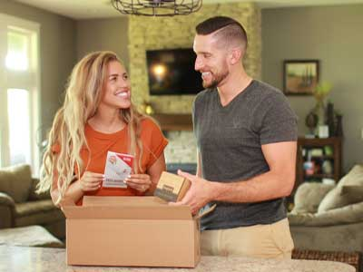 Man and woman opening a box containing a free energy efficiency kit provided by MidAmerican Energy.