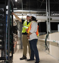 Two men in vests and hard hats looking at an energy management system in the control room of a building