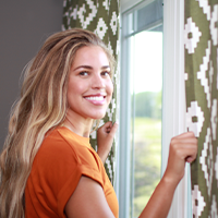 Smiling woman opening curtains, looking back