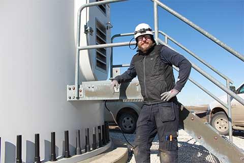 Jason Gruszeczka standing next to the entry way to a wind turbine
