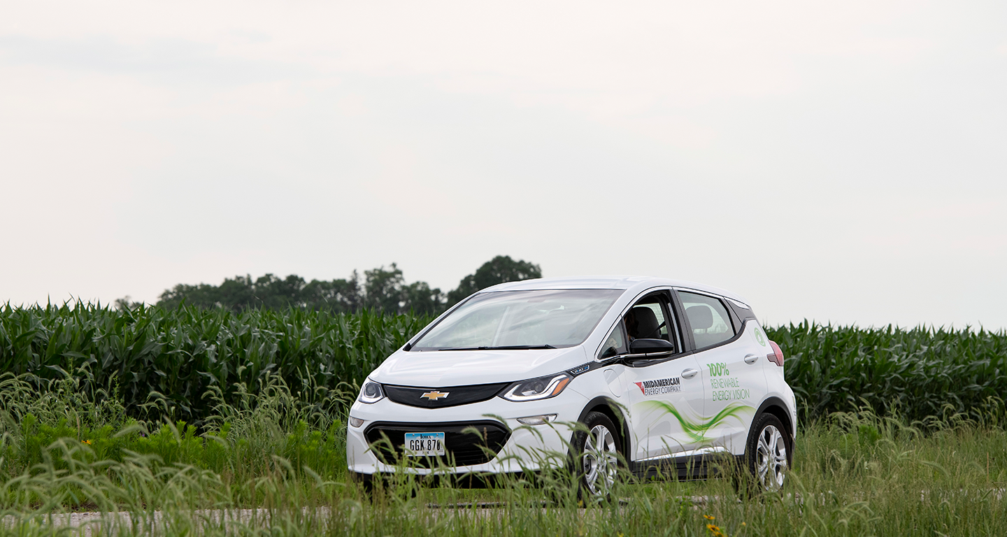 MidAmerican electric vehicle driving alongside a cornfield in summer
