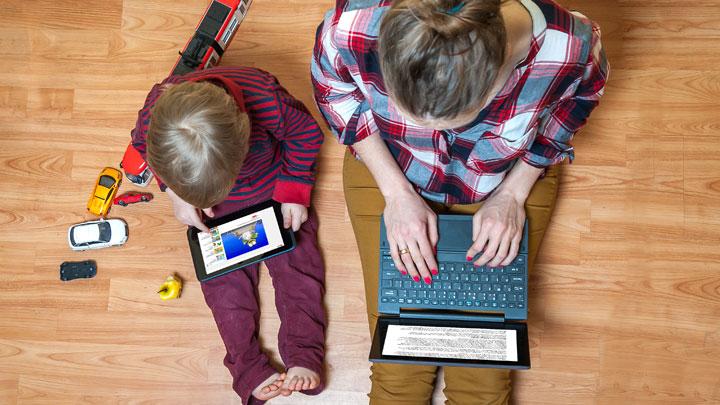 Mom, child sitting on floor on tablet