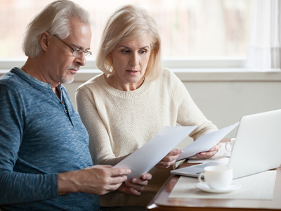 Couple looks over monthly bills with laptop