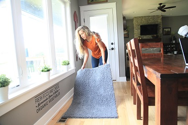 Woman clearing rug from floor register