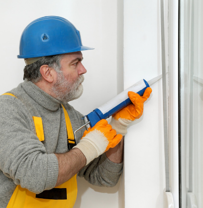 Worker sealing windows with caulk