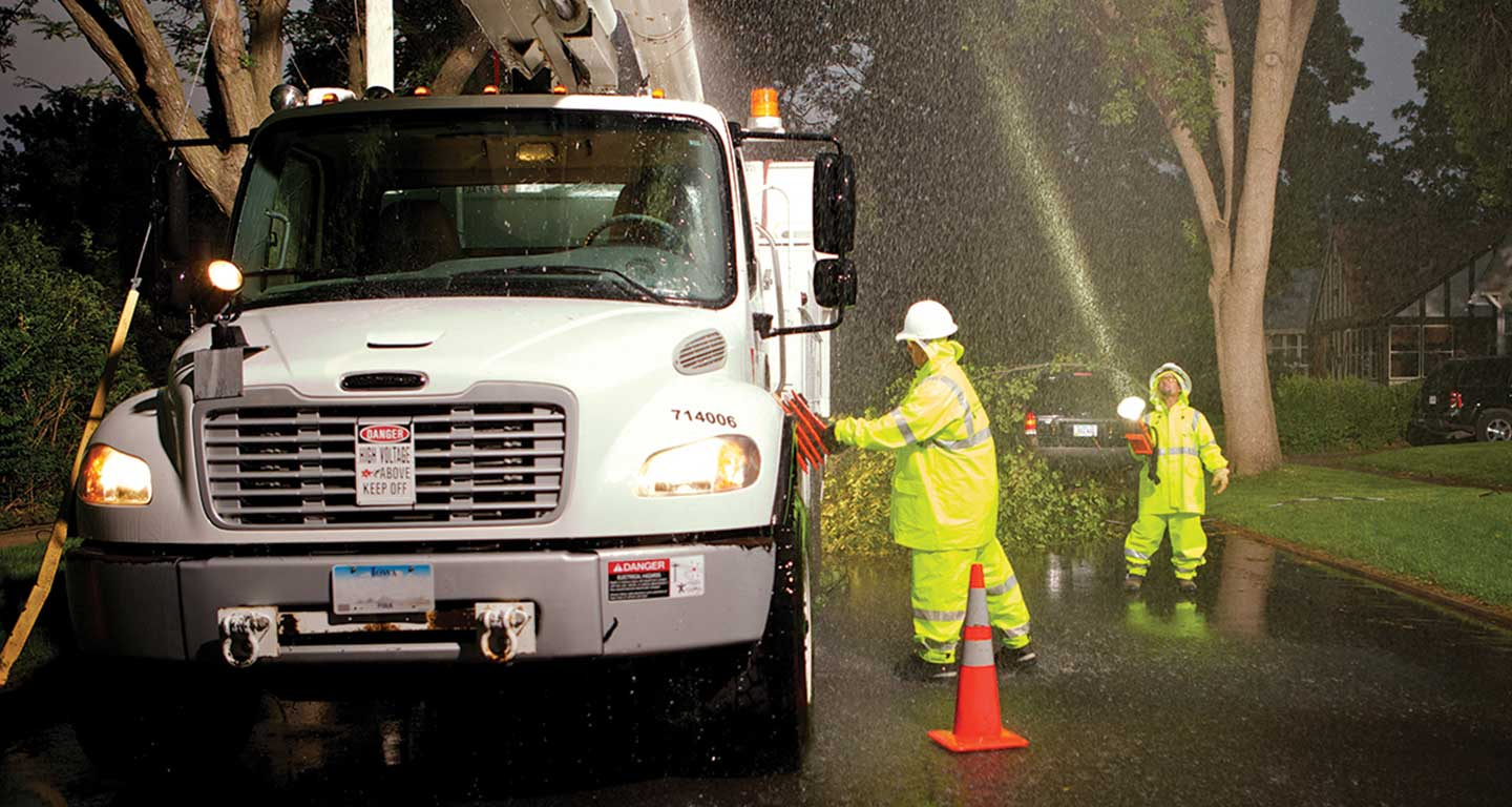 MidAmerican employees working in severe weather by a truck with fallen branches