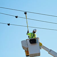 MidAmerican employee installing a smart sensor on a power line