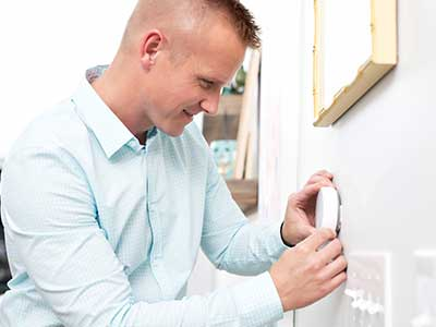 Man looking at smart thermostat