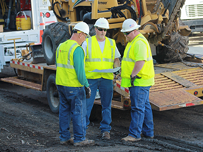 Three MidAmerican employees in safety vests and hardhats discussing a project at a work site.
