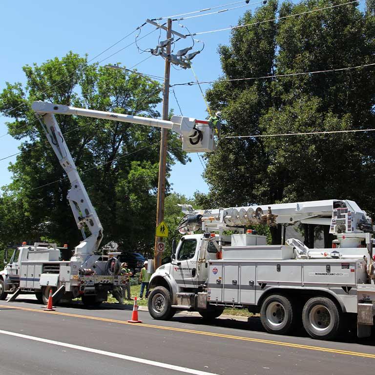 Lineman pole repair work, bucket trucks, sunny day