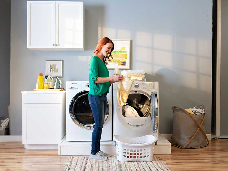 Woman folding clothes in front of a dryer