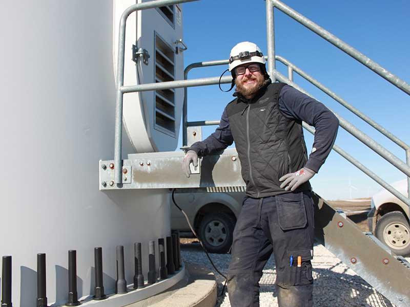 Jason Gruszeczka standing next to the entry way of a wind turbine