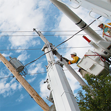 Worker in a bucket truck performing work on a utility pole with overhead wires