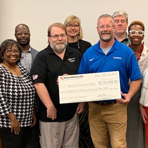 MidAmerican employee presenting a check to a group of Waterloo Career Center representatives.