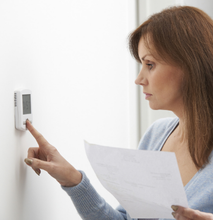 Woman setting thermostat to 68